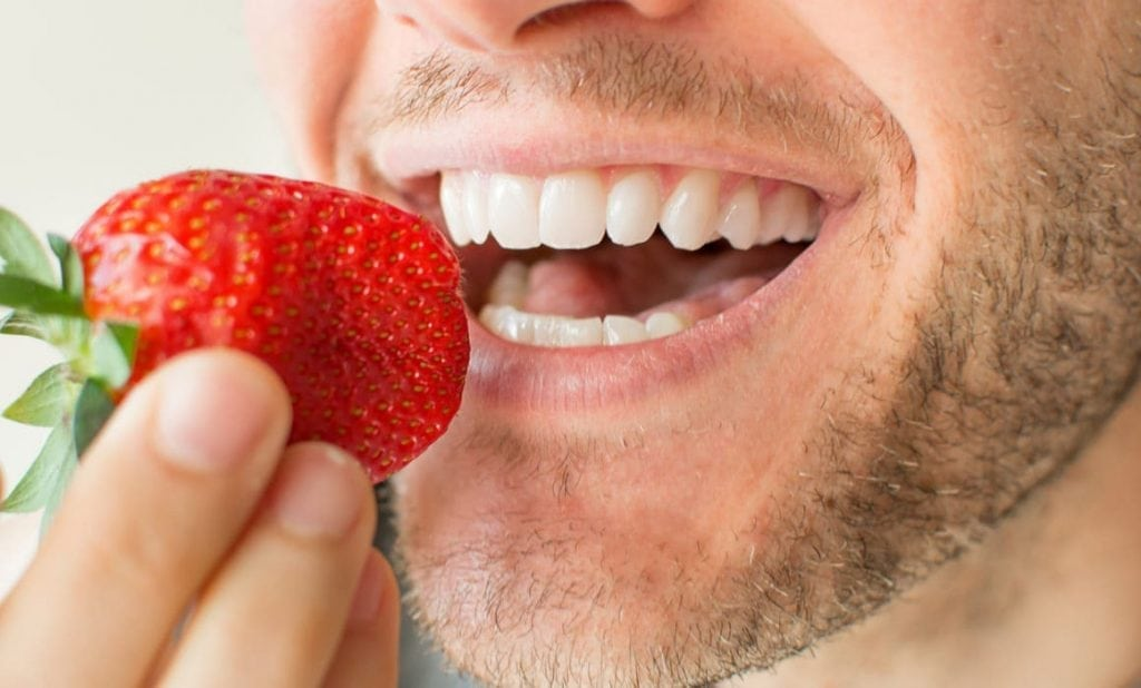 A man eats a strawberry that contains acids to whiten teeth