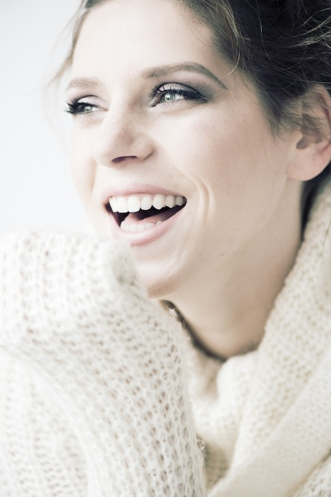 Woman smiles confidently after receiving dental bonding.